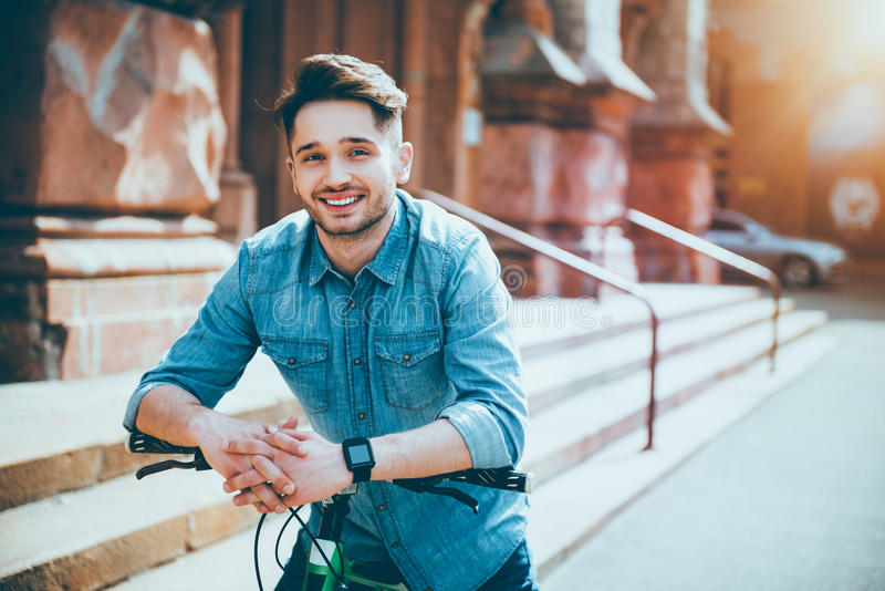 Smiling young man sitting on the bicycle royalty free stock photos