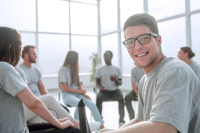 Smiling young man sitting in a circle of like-minded people. Close up. smiling young men sitting in a circle of like-minded people. business and education royalty free stock photography