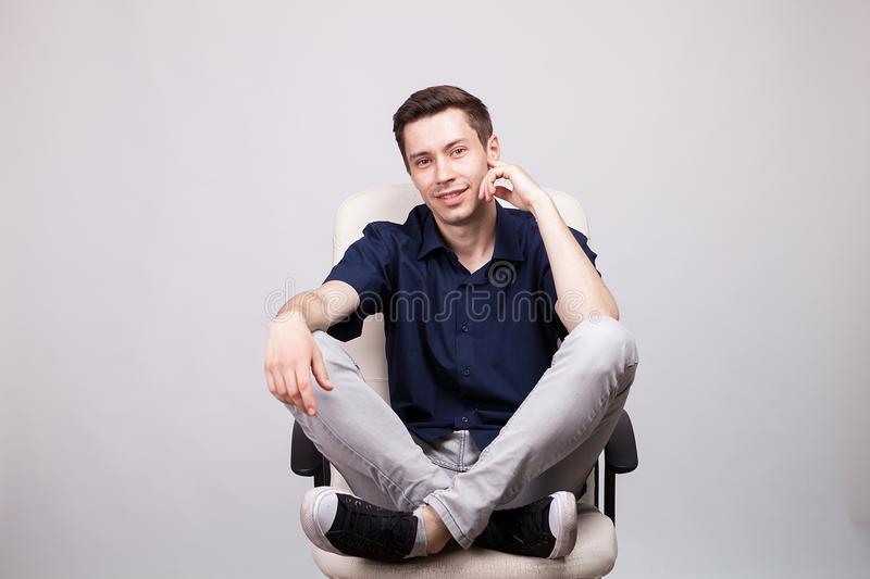 Smiling young man sitting with his feet up on an office chair royalty free stock photos