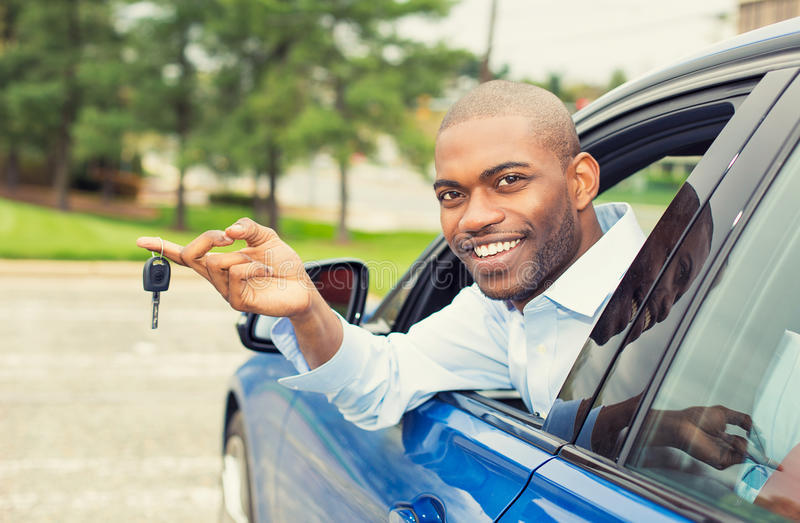 Smiling, young man sitting in his new car showing keys. Closeup portrait happy, smiling, young man, buyer sitting in his new blue car showing keys isolated stock photos
