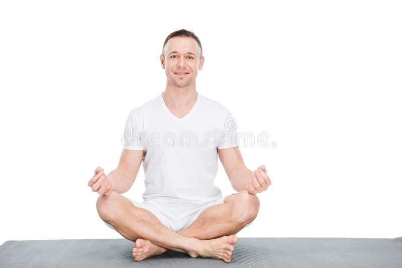 Athletic young man sitting on yoga mat and meditating royalty free stock photo