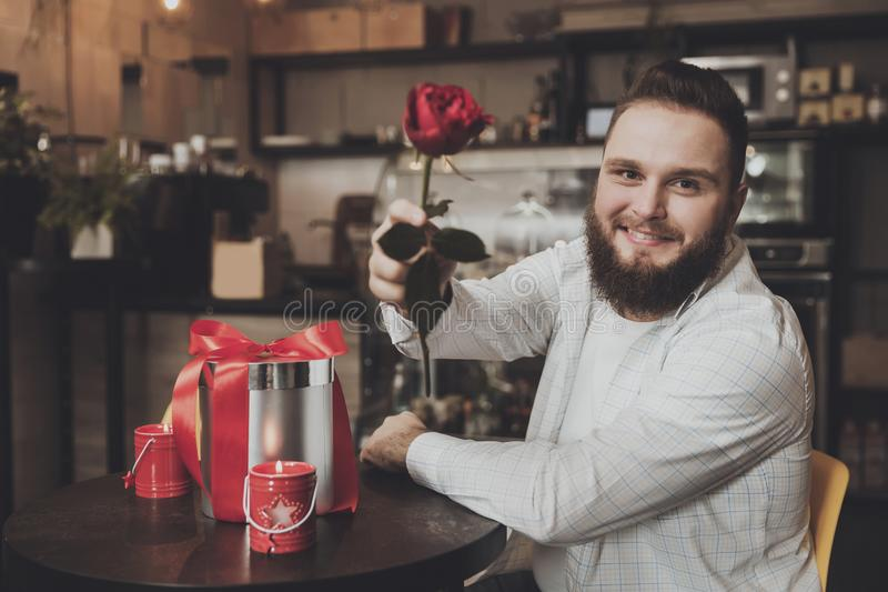 Smiling young man sitting the table holding a rose royalty free stock photo
