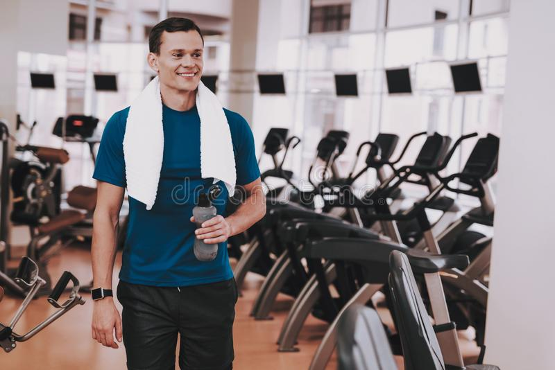 Smiling Young Man in Sport Club near Treadmills royalty free stock image