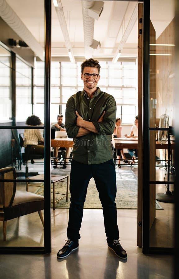 Smiling young man standing in doorway of office stock photos