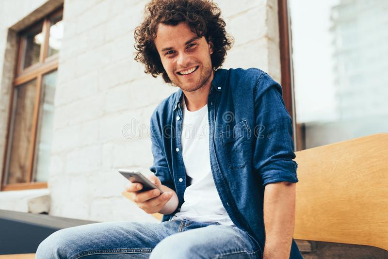 Smiling young man stitting outdoors texting on mobile phone. Happy male with curly hair using smart phone application for stock photos