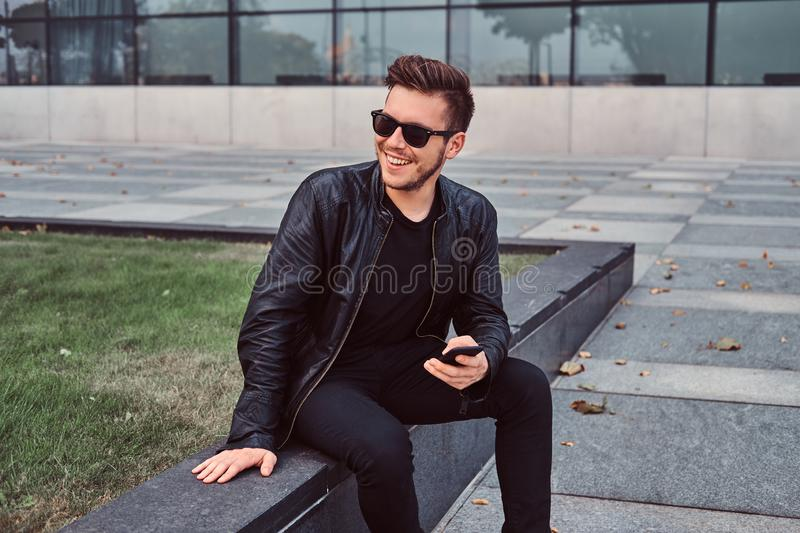 Smiling young man in sunglasses with stylish hair dressed in black leather jacket holds smartphone while sitting near a royalty free stock image