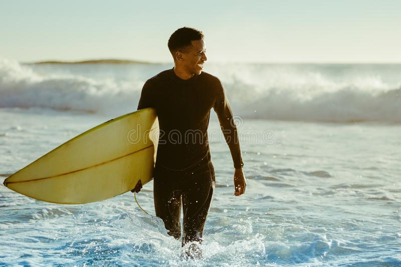 Surfer coming out of the ocean royalty free stock images