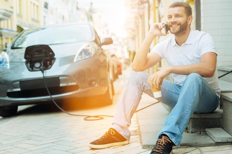 Smiling young man talking on the phone. Positive conversation. Friendly positive young man talking on the phone while his electric car charging stock photography