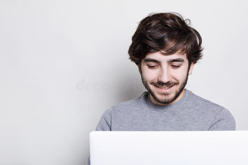 Smiling young man with trendy beard and hairstyle making video call with friends being happy and pleased to talk with friends. Clo. Se-up of smiling bearded man royalty free stock photos