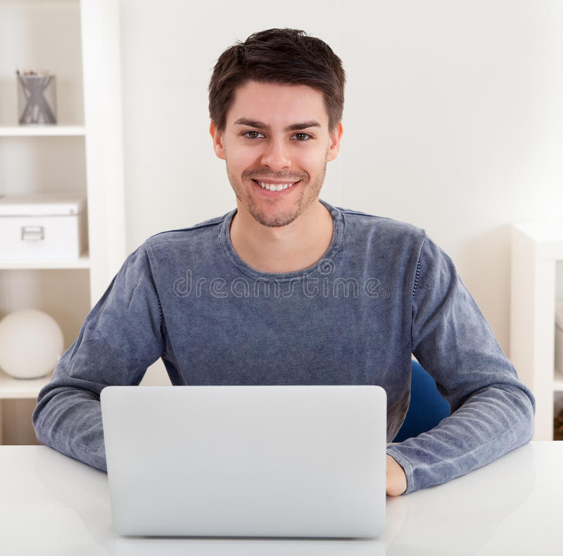 Smiling young man using a laptop royalty free stock photo