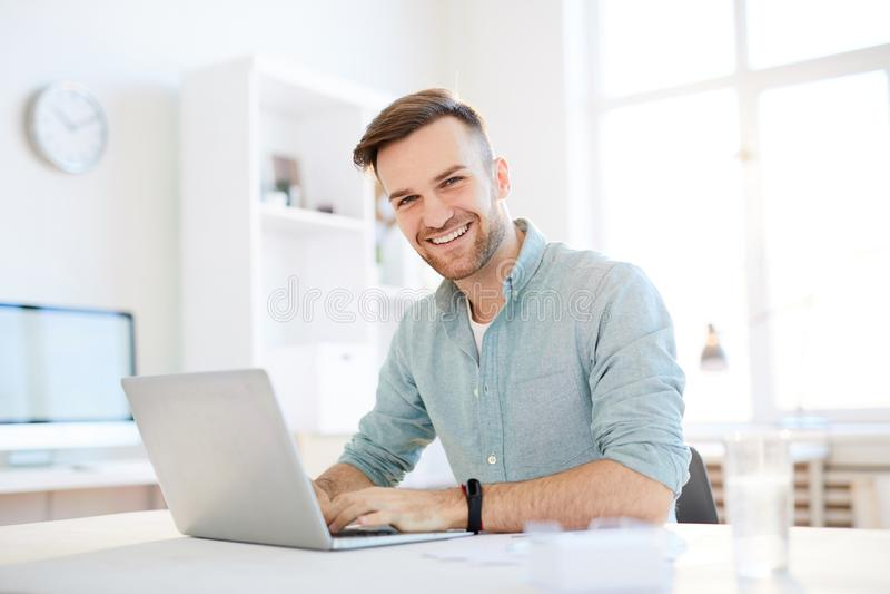 Smiling Young Man Using Laptop stock photo