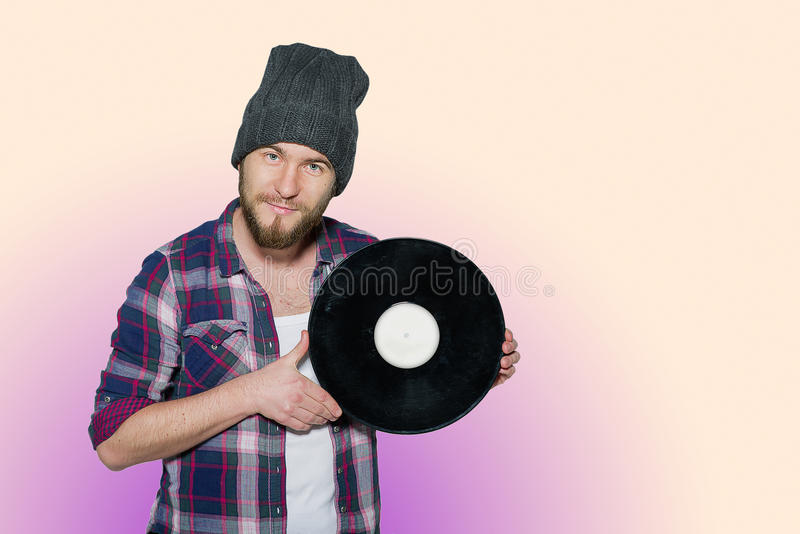 Smiling young man with vinil isolated on colorful background. Smiling young man with a beard wearing in a plaid shirt and hat with vinil isolated on colorful royalty free stock photo
