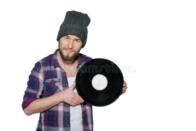 Smiling young man with vinil isolated on white background. Smiling young man with a beard wearing in a plaid shirt and hat with black vinil isolated on white royalty free stock image