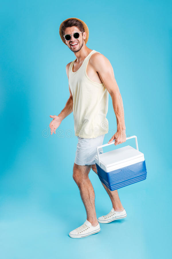 Smiling young man walking and holding cooler bag. Smiling young man in hat and sunglasses walking and holding cooler bag stock photography