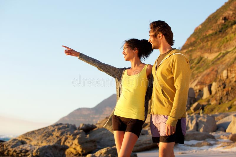 Smiling young man and woman at the beach enjoying view royalty free stock photography