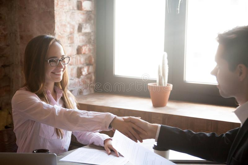 Smiling young man and woman handshake, successful deal stock image