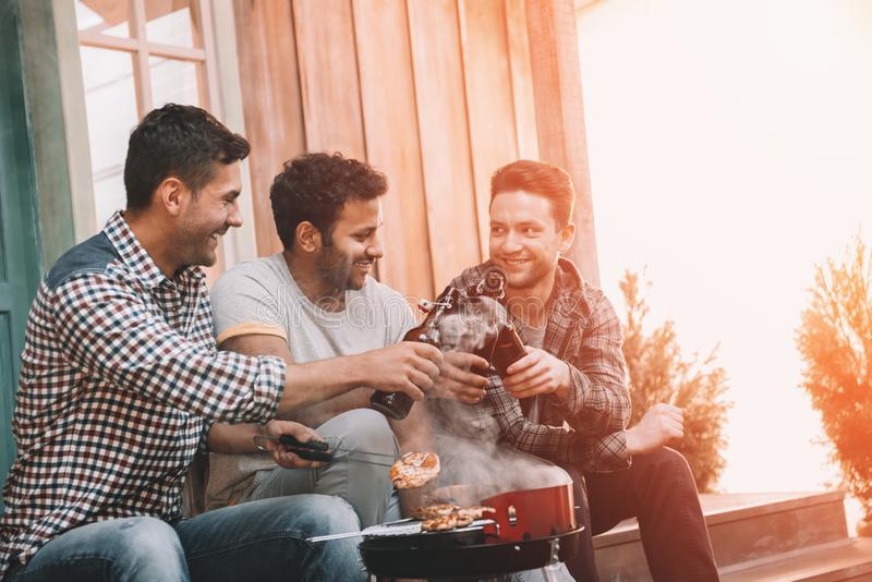 Smiling young men clinking beer bottles and grilling meat stock image