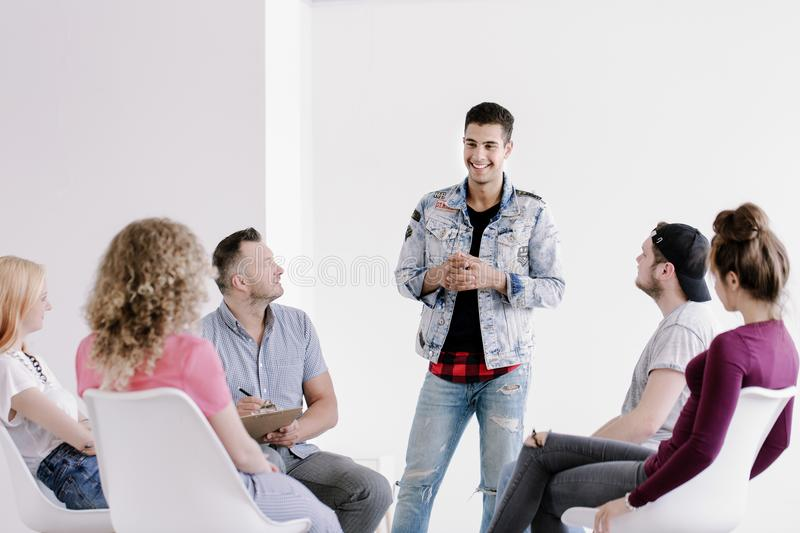 Smiling young man talking. Smiling young men in jeans and denim jacket standing and talking about his progress during group therapy for rebellious youth royalty free stock photography