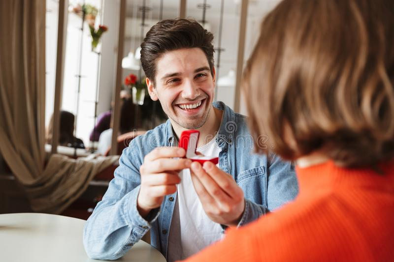 Smiling young man proposing to a woman. Smiling young men proposing to a women while sitting together at the cafe table stock photography