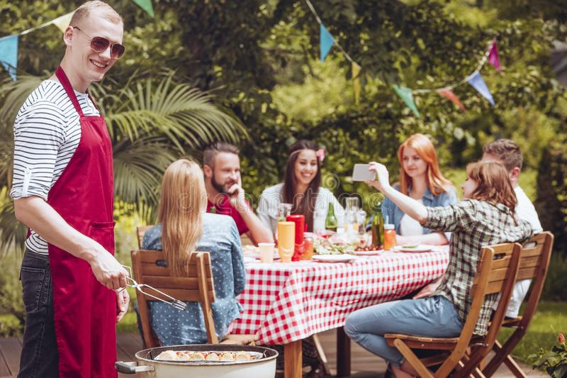 A smiling young man wearing an apron grilling shashliks in the f royalty free stock images