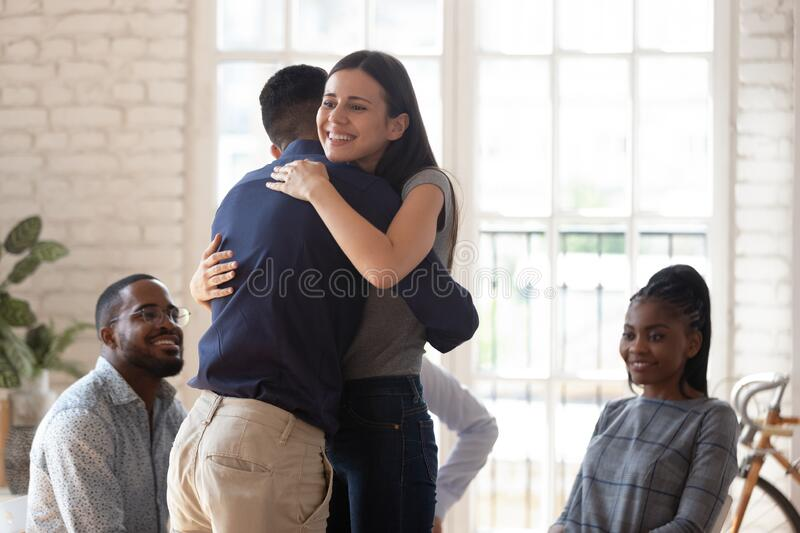 Happy man and woman hug showing support at therapy session. Smiling young men and women hug show love and care involved in psychological therapy session in royalty free stock images