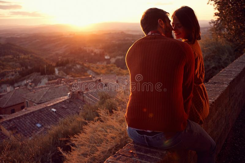 Smiling man and woman hugging and kissing at sunset stock photo