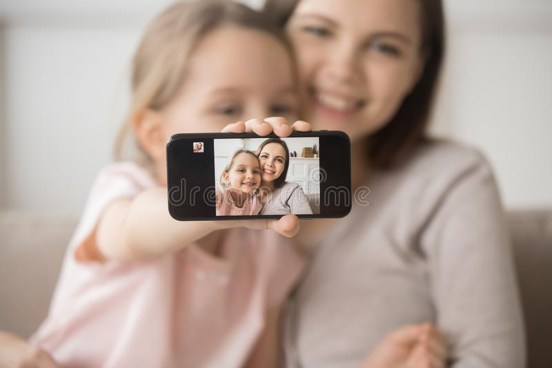 Smiling young mom and little daughter make cellphone selfie together stock photography