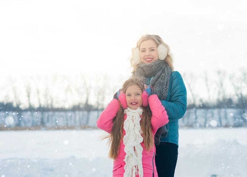 Young family enjoying a day out the ice area in a snowy park royalty free stock images