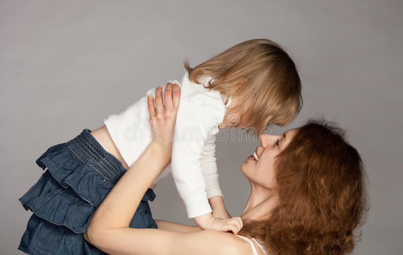 Smiling young mother raising her little daughter stock photo