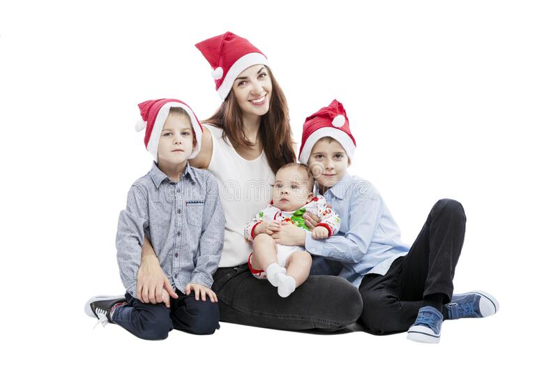 A smiling young mother with three young children in santa claus hats is sitting on the floor. Tenderness and family happiness. New. Year and Christmas stock photo