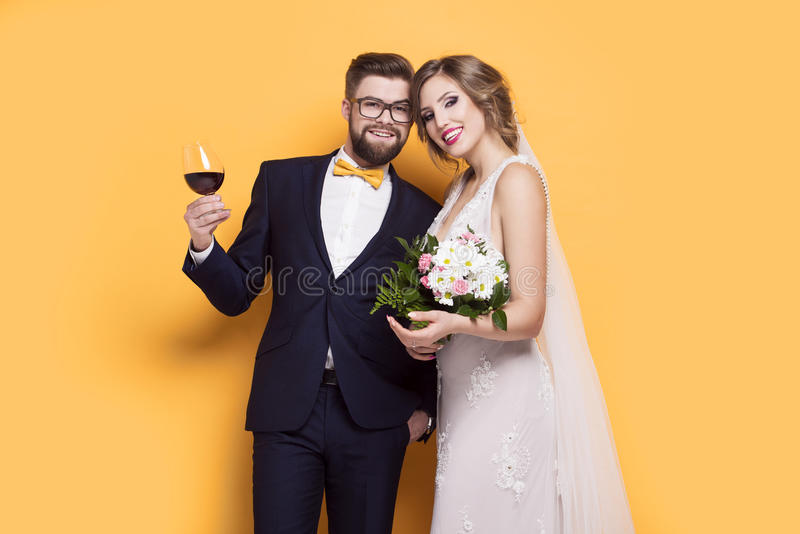 Smiling young newly married on a yellow background royalty free stock photography