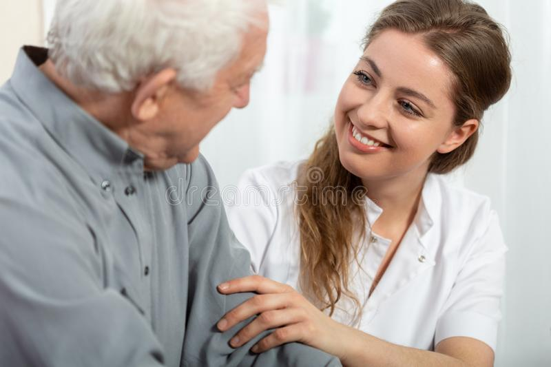 Smiling nurse sitting at table with senior patient stock photos