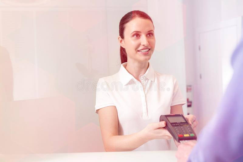 Smiling young patient paying fees through credit card at checkout counter in clinic. Smiling young patient paying fees through credit card at checkout counter royalty free stock images