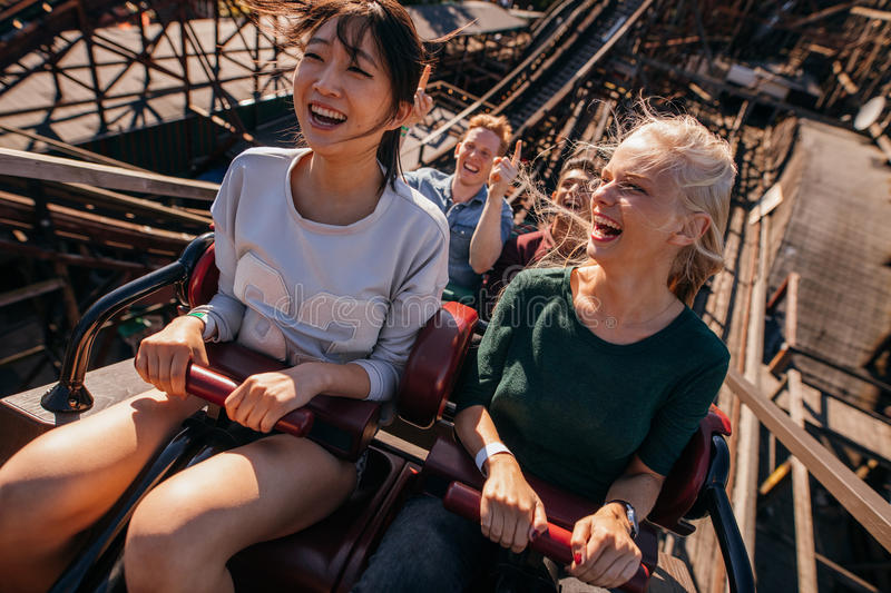 Smiling young people riding a roller coaster stock images