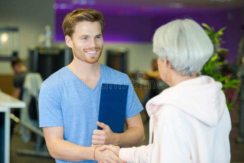 Smiling young physical trainer shaking hands fit senior man stock photography
