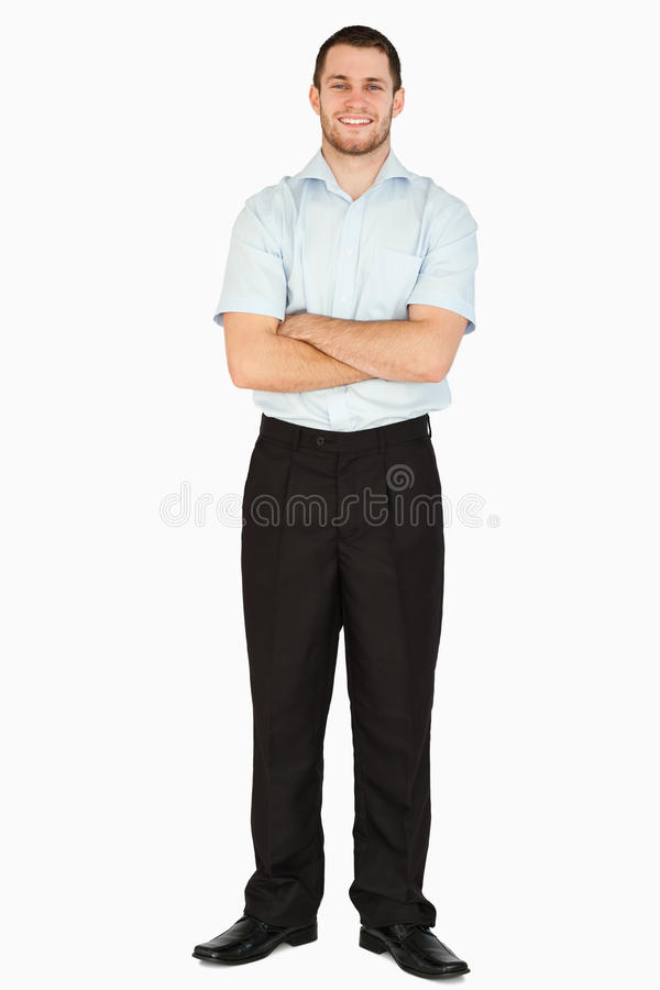 Smiling young post employee with arms folded. Against a white background stock image