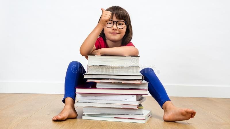 Smiling child sitting behind many books with a thumbs up stock image