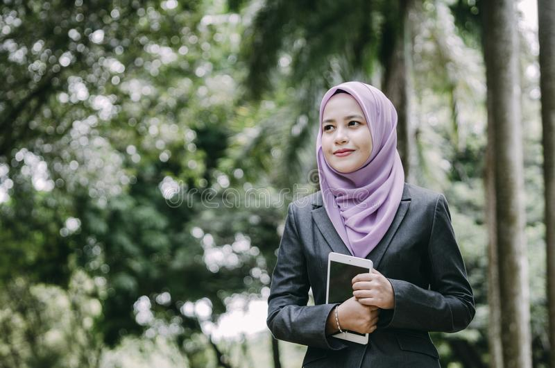 smiling young professional muslimah businesswoman holding a tablet in the park royalty free stock photo