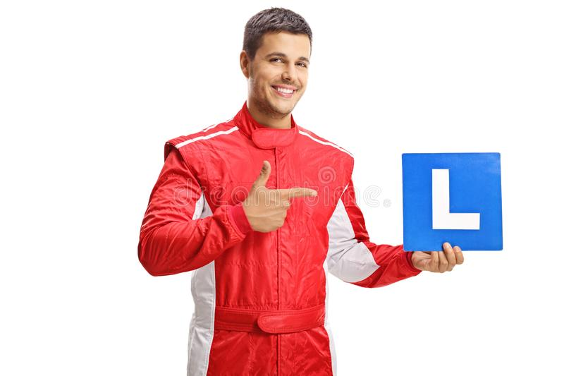 Smiling young racer holding a learner plate and pointing royalty free stock image