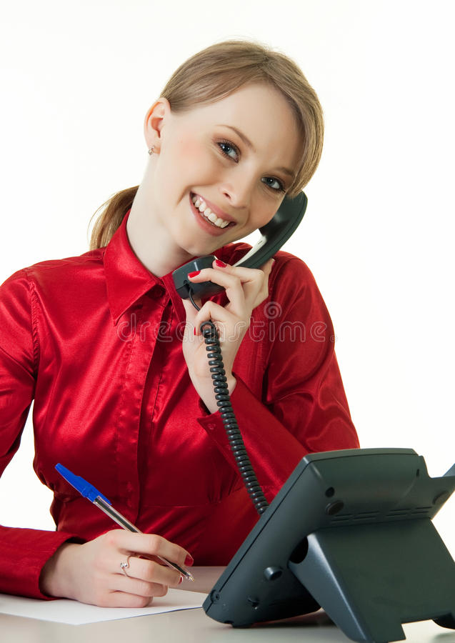 Smiling young receptionist using desk phone. On white background stock images