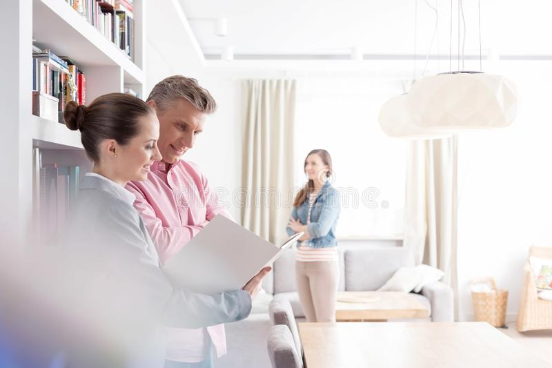 Smiling young saleswoman and male client looking at blueprint while woman standing in apartment. Smiling young saleswoman and male client looking at blueprint royalty free stock photos