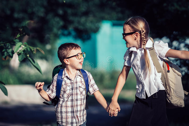 Smiling young school children in a school uniform jumping on the. Road at the day time. Concept of the children are ready to go to school royalty free stock image