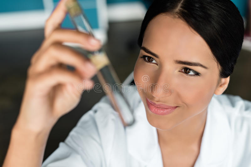 Smiling young scientist holding test tube in chemical laboratory stock photography