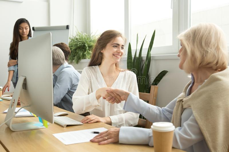 Smiling young and senior businesswomen shaking hands in coworkin. Smiling young and old businesswomen shaking hands after signing contract in coworking office royalty free stock images