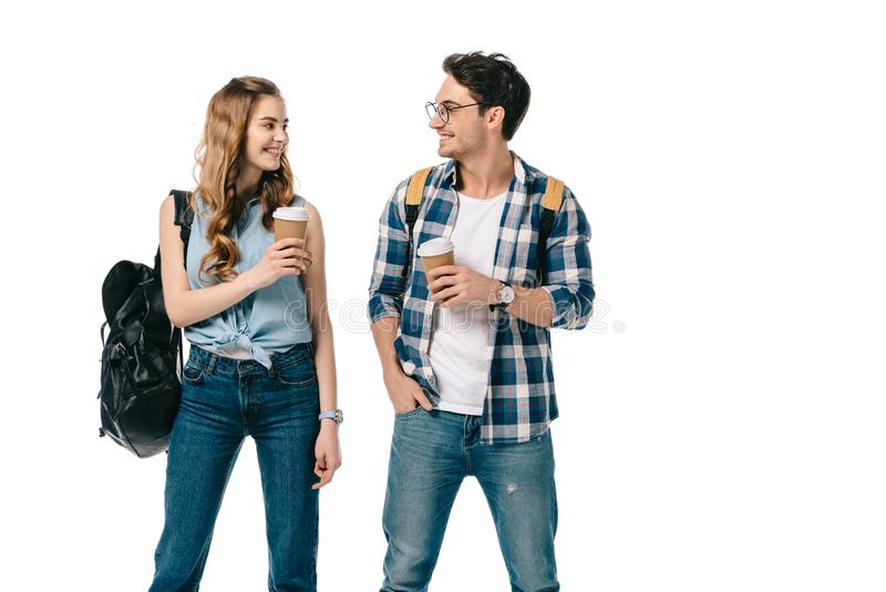 smiling young students holding coffee to go and looking at each other stock photo