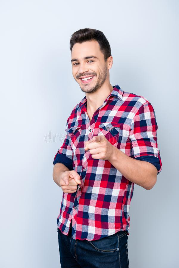 Smiling young stylish bearded brunet student in bright casual ch. Eckered shirt is standing on light background and point on camera with flirty smile and glance stock photo