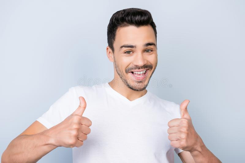 Smiling young stylish bearded brunet student in casual white t. Shirt is standing on light background and show thumbs up with flirty smile and glance royalty free stock photography