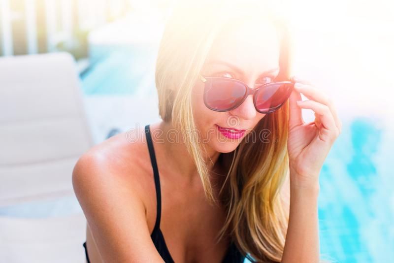 Smiling Young Suntanned Woman in Sunglasses. Young Suntanned Woman in Black Sunglasses near Swimming Pool Summer Day Care Concept stock photo