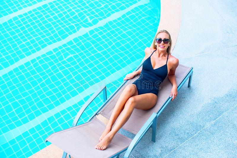 Smiling Young Suntanned Woman in Sunglasses. Smiling Happy Young Suntanned Woman in Black Bathing Suit and Sunglasses On the Plank Bed Near Swimming Pool Have stock photos