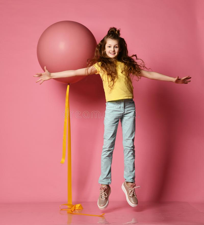 Smiling young teen girl in blue jeans and yellow t-shirt with her hands spread levitates the same as big helium balloon near her royalty free stock photos